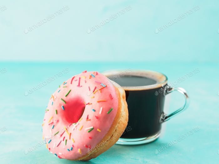 pink donut and coffee on blue background , copy space