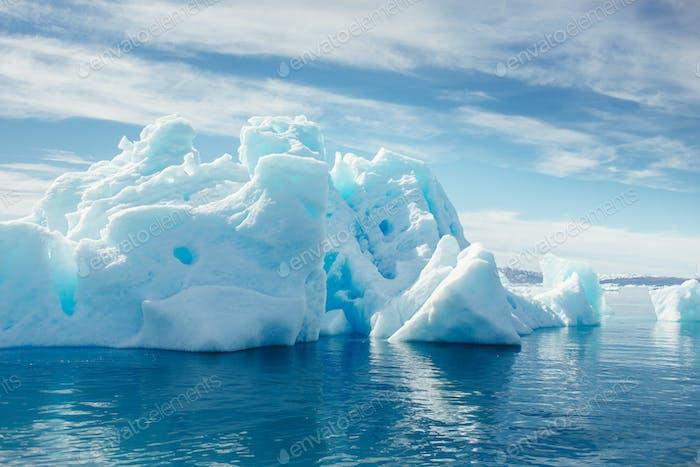 Majestätische Eisberge schweben auf dem Meer gegen bewölkten Himmel