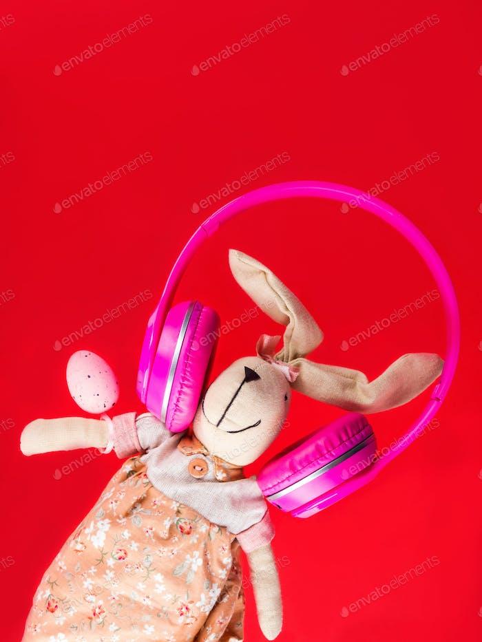 Osterhase mit rosa Kopfhörern. Urlaubskonzept
