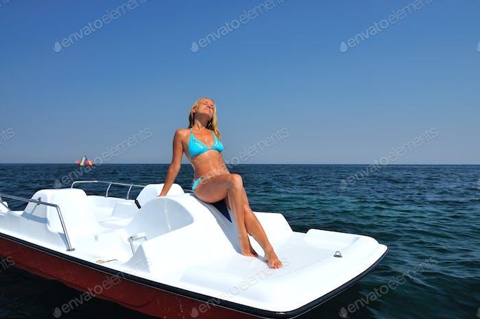 Young blond woman in blue bikini sitting on white catamaran and enjoying sunshine
