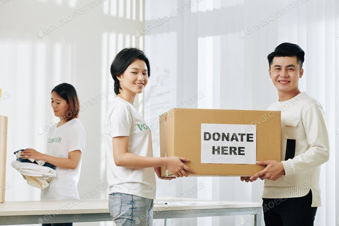 Happy volunteers carrying box