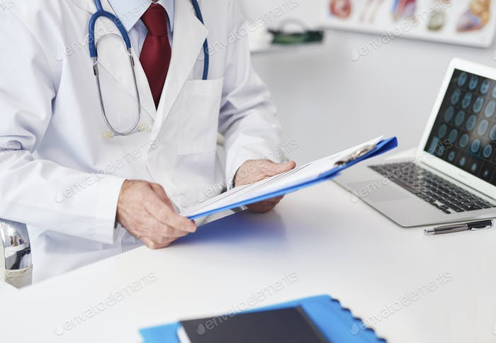 Close up of doctor examining the medical record