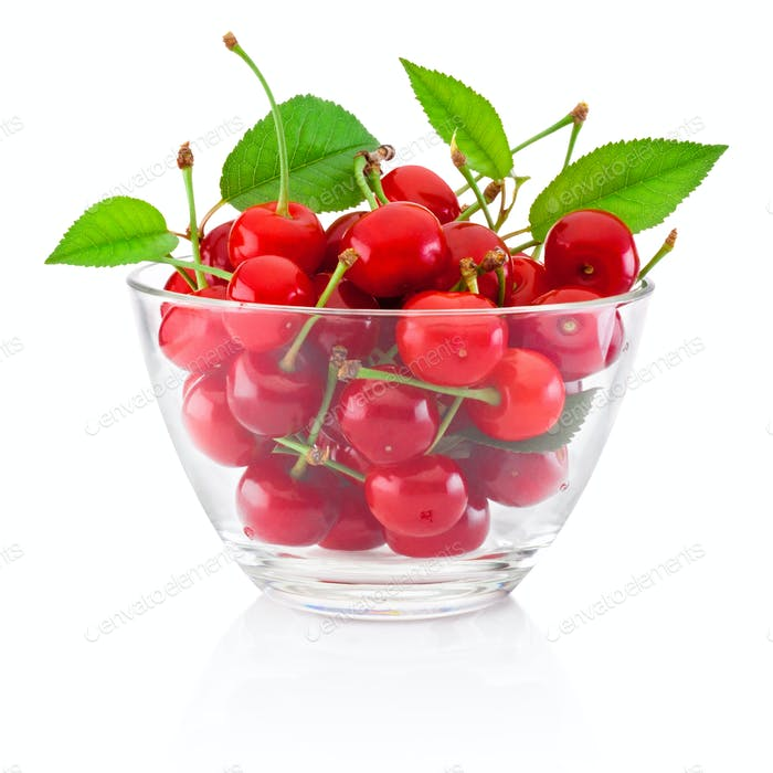 Fresh ripe cherries with leaves in glass bowl isolated on white