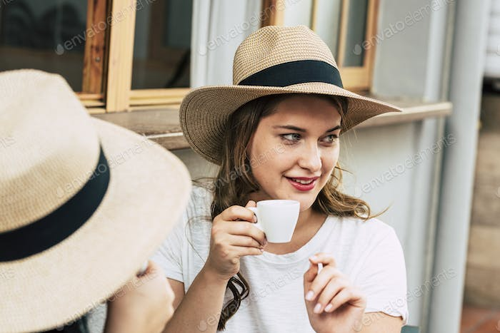 Cheerful beautiful young woman portrait drinking coffee at the bar with friend