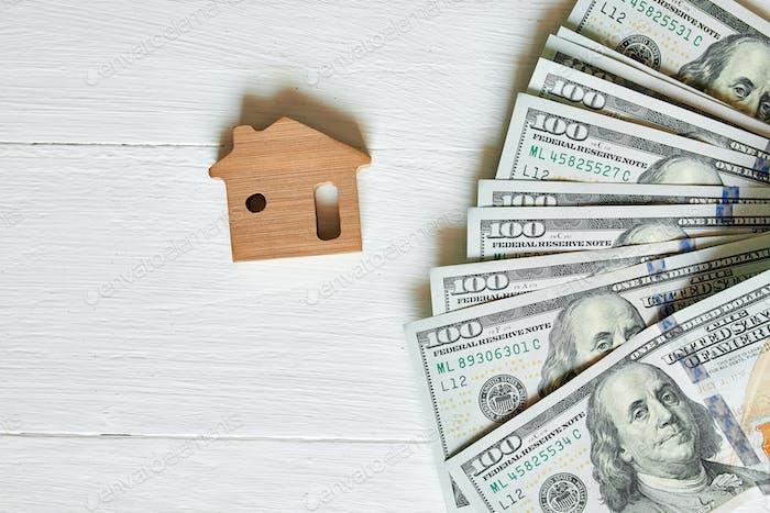 Kleines Holzhaus und hundert Dollar auf weißem Hintergrund