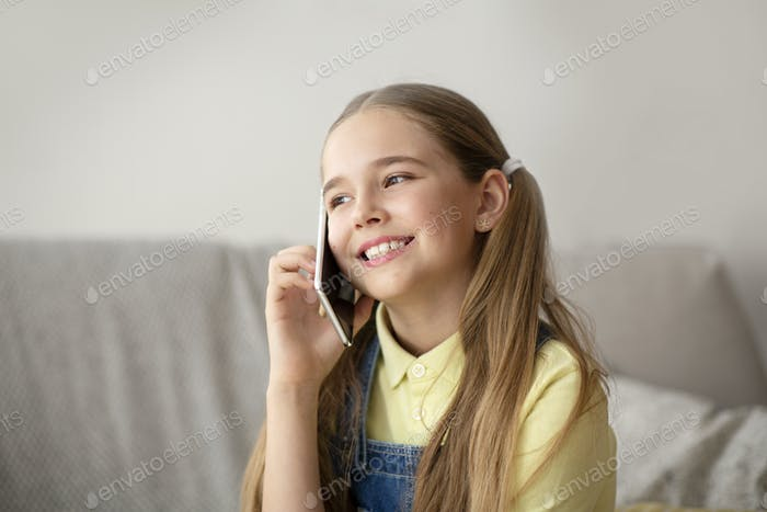 Girl talking on cell phone sitting on couch