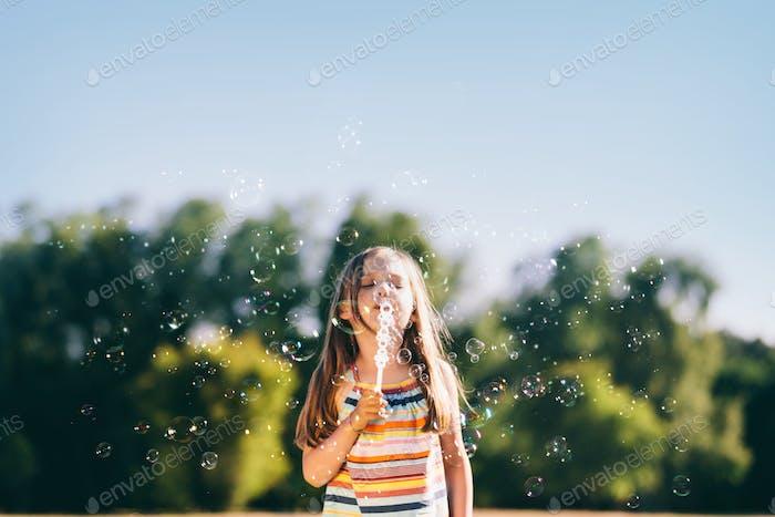 Маленькая девочка дует мыльные пузыри в парке.
