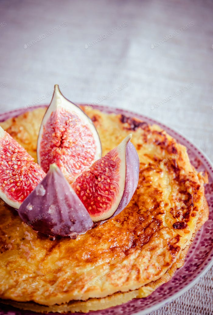 Pile of pumpkin crepes decorated with fresh fig