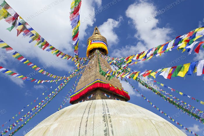 Low angle view of colourful prayer flags on stupa of Buddhist temple.
