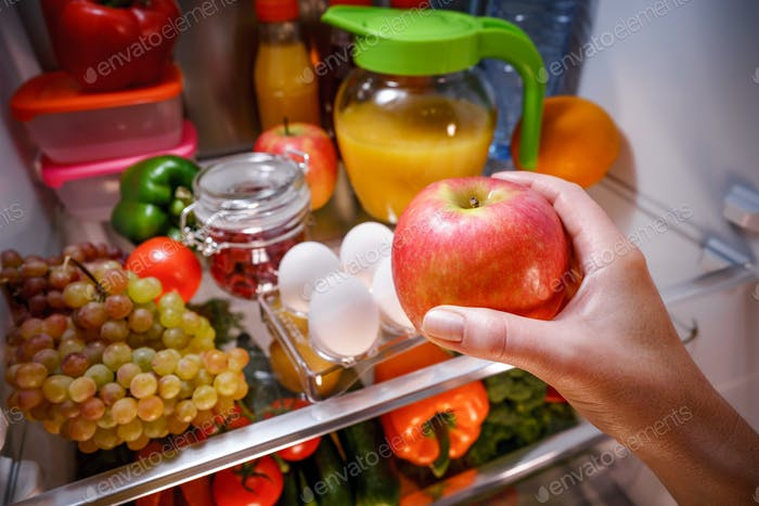 Woman takes the apple from the open refrigerator.
