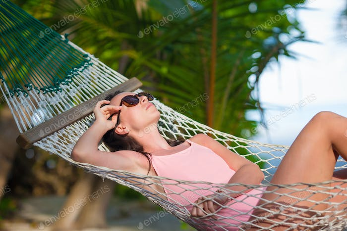 Woman in swimsuit relaxing on hammock sunbathing on vacation