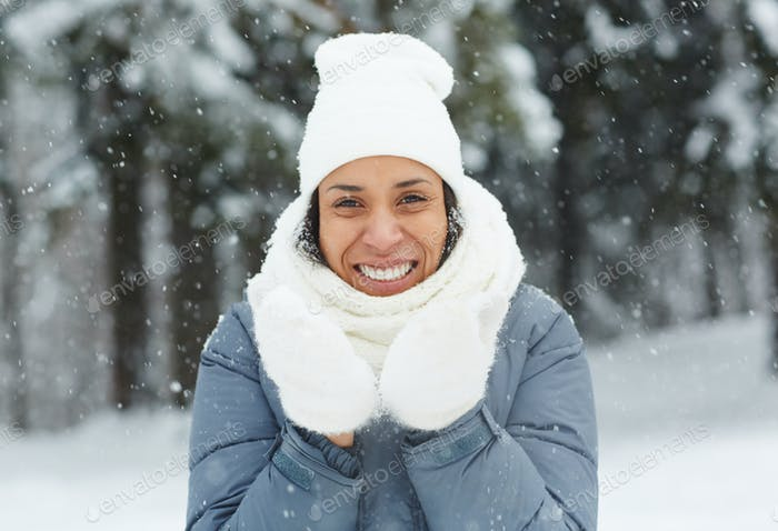 Attractive woman in mittens looking at camera
