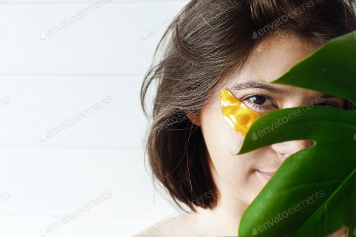 Young woman with natural makeup and golden eye patches at green monstera leaf