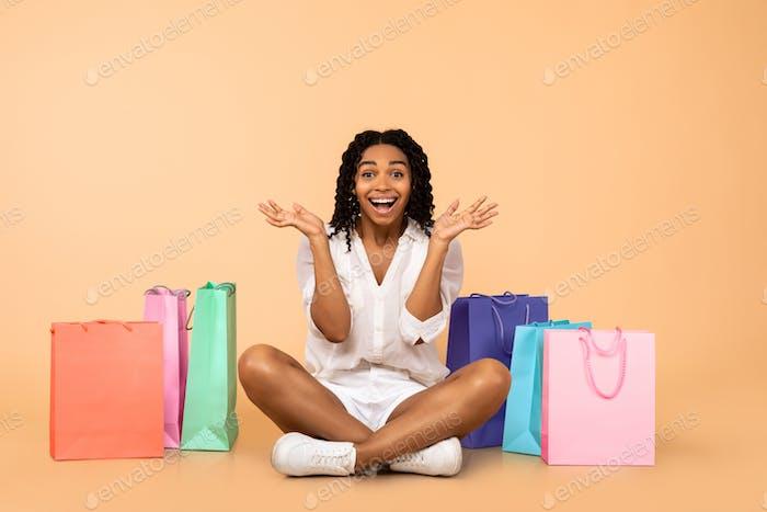 Schwarzes Mädchen sitzt unter Einkaufstaschen Schreien In Aufregung, Studio