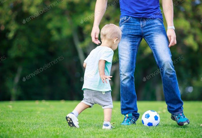 Junge Mann und Kleinkind Sohn spielen Fußball im Park