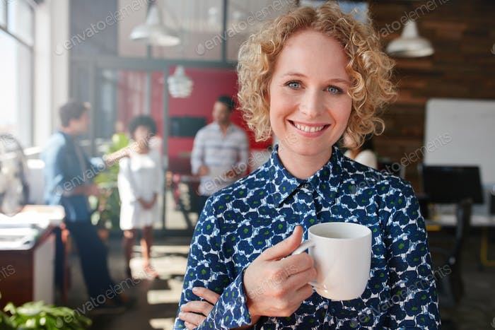 Happy young businesswoman having coffee