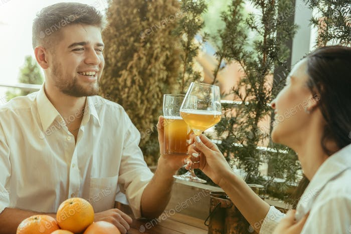 Young friends or couple drinking beer and celebrating together