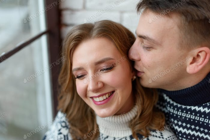Image of young happy man kissing and hugging beautiful woman