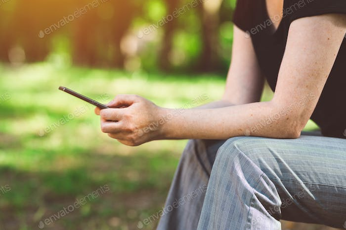 Woman using smartphone in public park
