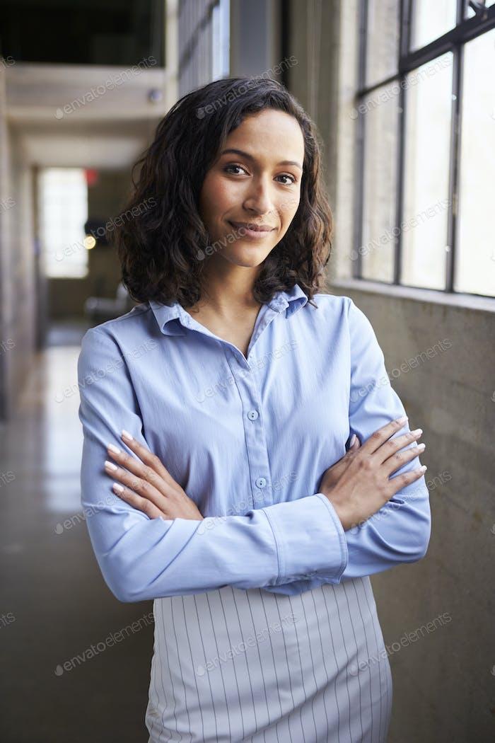 Junge gemischte Rasse Geschäftsfrau stehend mit Armen gekreuzt