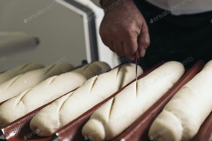 Bäcker Teig in einer Bäckerei kneten.