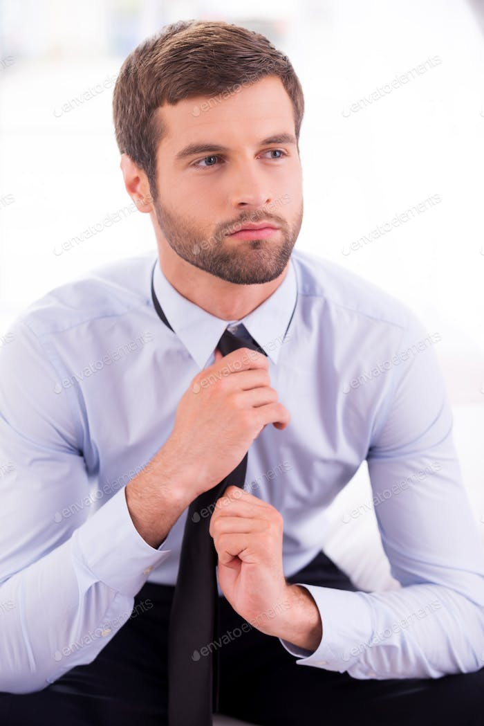 Businessman tying a necktie. Thoughtful young businessman tying a necktie while sitting on the bed