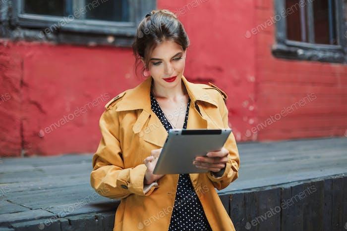 Junge attraktive Frau in orange Trenchcoat und schwarzen Punkten