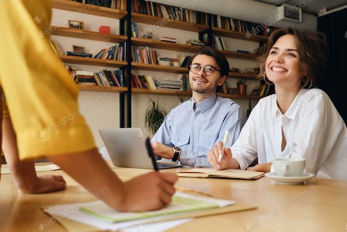 Young business colleagues sitting at the desk happily looking at boss working with papers in office