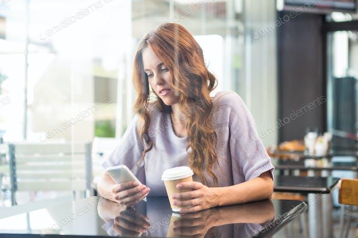 Pretty brunette enjoying a coffee in a coffee shop