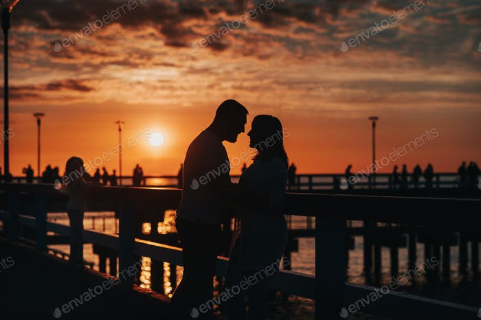 Portrait silhouette of a beautiful newlywed couple. A loving man hugs a girl at sunset, against the