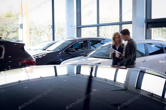 Saleswoman discussing over brochure with customer in showroom