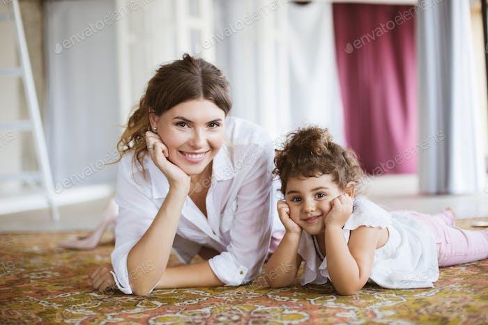 Junge lächelnde Mutter und hübsche kleine Tochter in weißen Hemden