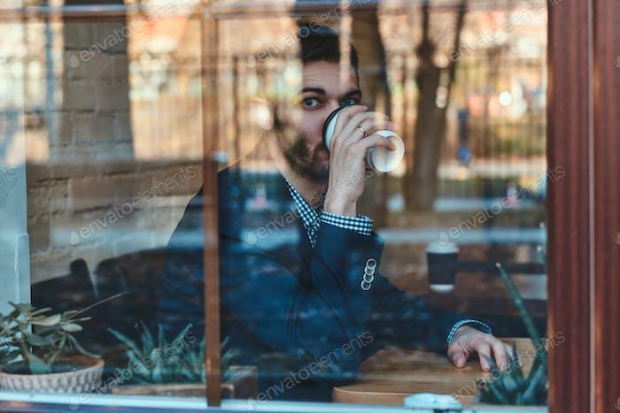 El hombre está bebiendo café en la cafetería