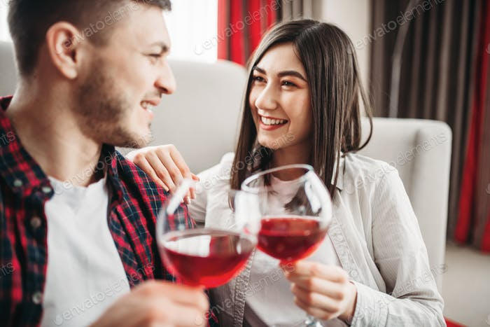 Love couple watches movie and drinks red wine