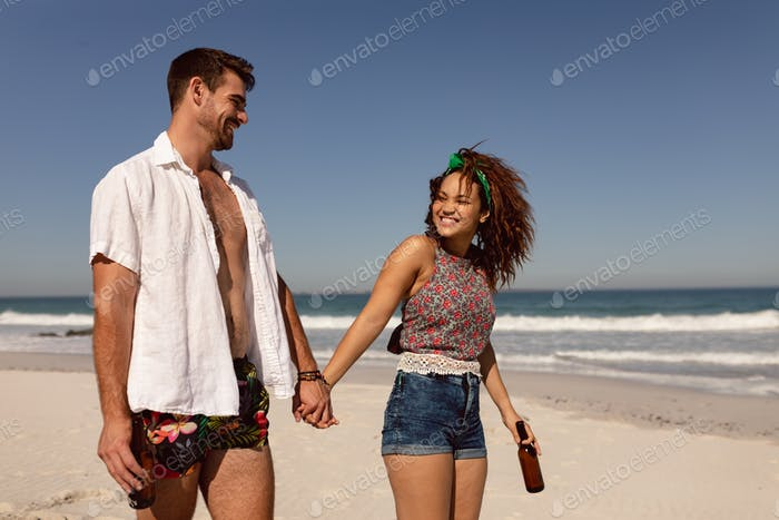 Front view of happy young Mixed-race couple with beer bottle walking on beach in the sunshine