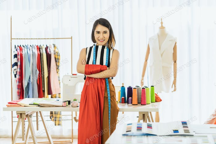 Portrait Young Asian Designer woman are arms crossed at workplace over Clothes mannequins