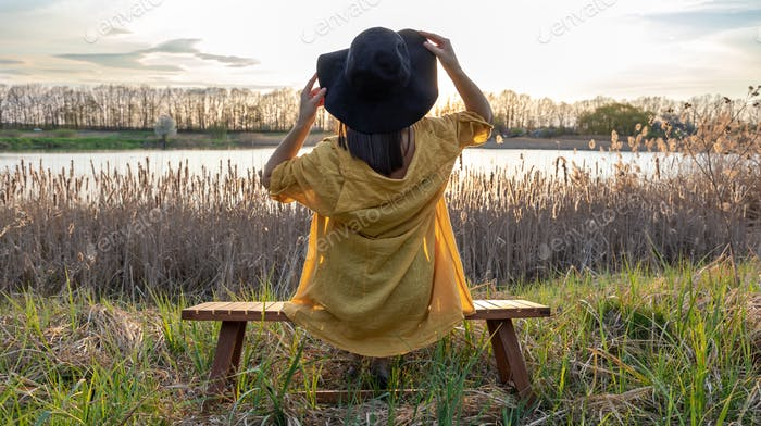 A stylish girl in a hat enjoys the sunset by the lake, view from the back.