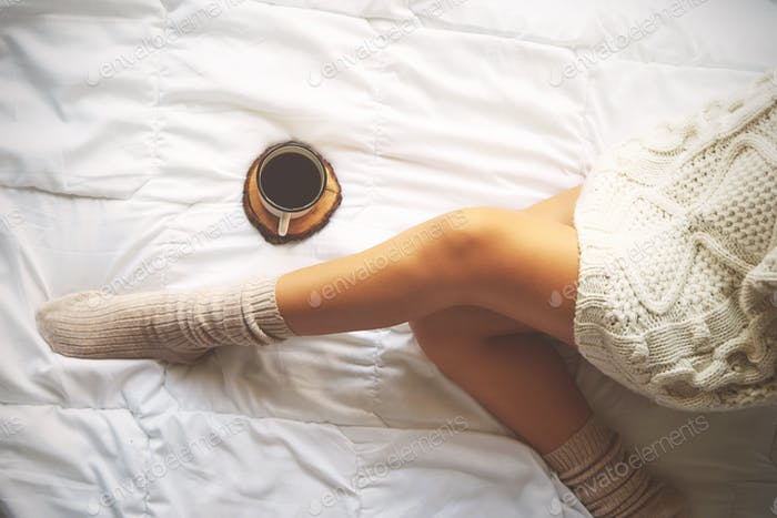 Soft photo of woman on the bed with cup of coffee, top view poin
