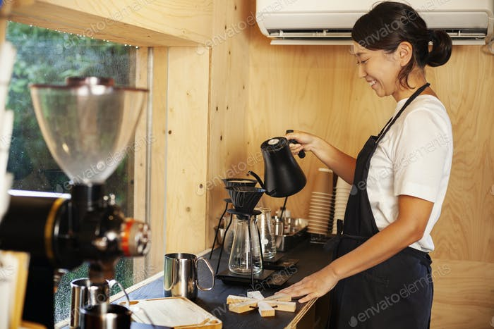 Japanese woman wearing apron standing in an Eco Cafe, preparing coffee.