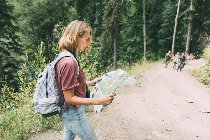 A woman on a tourist trail with a backpack holds a map. Local travel.
