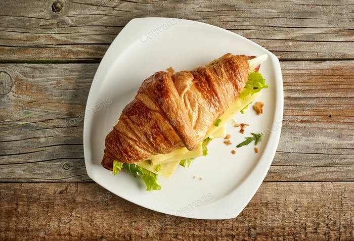 Croissant sandwich with cheese on wooden table