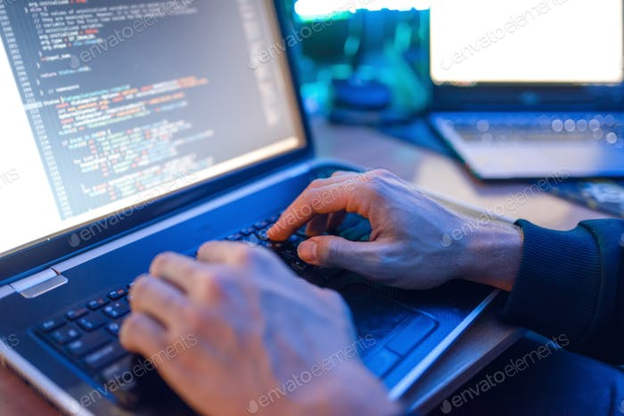 Hacker sitting at laptop, information hacking