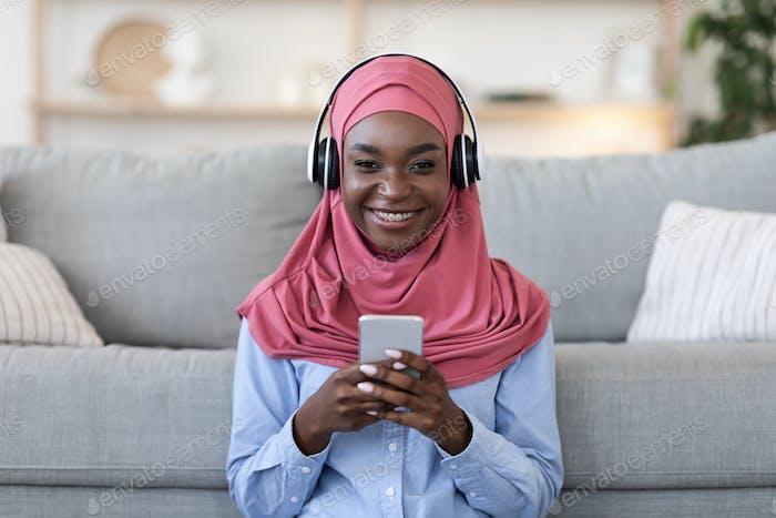 Black muslim woman enjoying listening music on smartphone with headphones at home