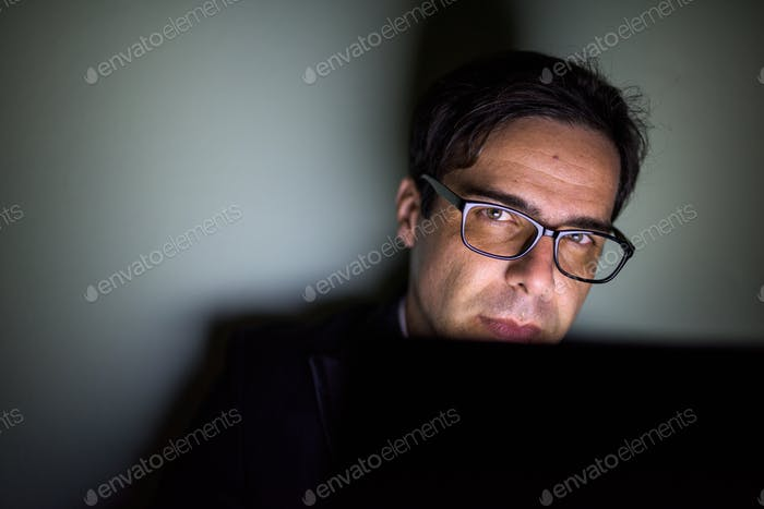 Handsome Persian businessman using laptop in dark room