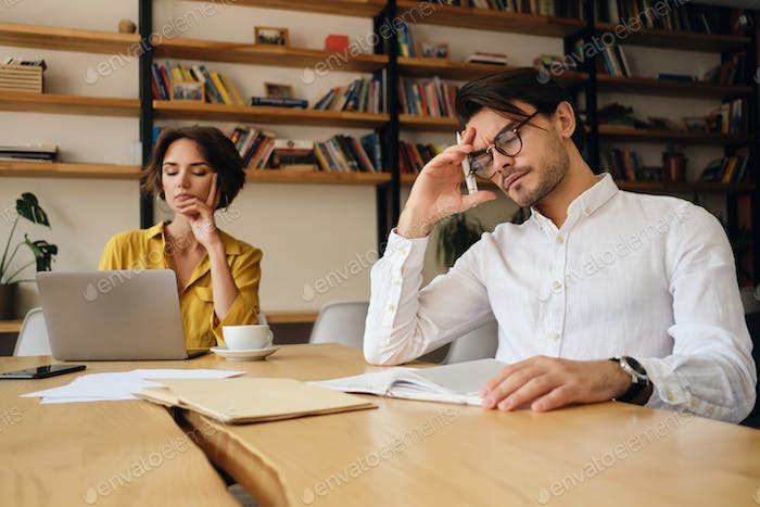 Young tired man in eyeglasses leaning head on hand thoughtfully working in office