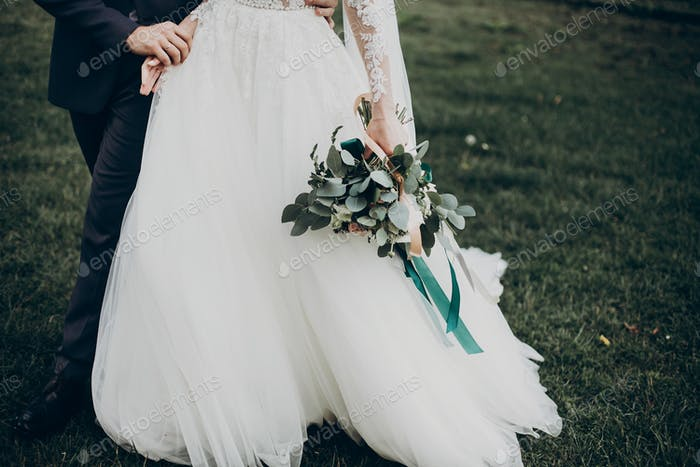 Stylish happy bride and groom walking in yard and holding hands at wedding ceremony