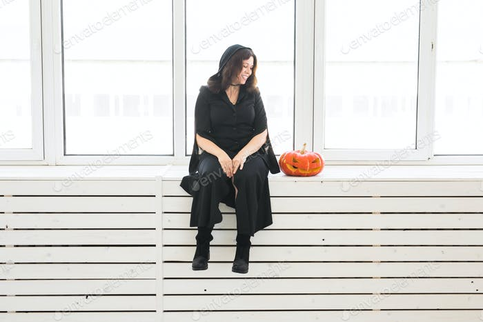 Halloween and holidays concept - Witch woman with Jack O'Lantern pumpkin