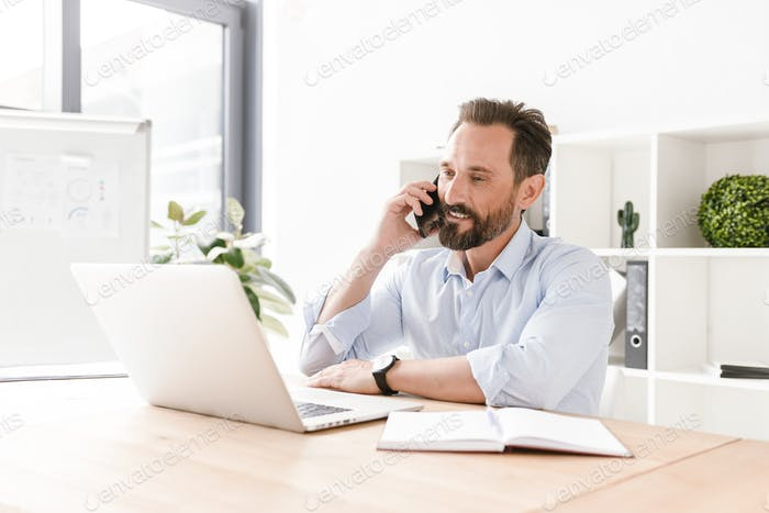 Confident businessman talking on mobile phone