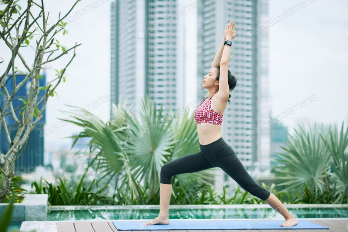 Asian woman doing yoga in the city