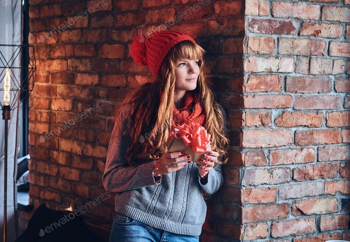 Rotschopf weiblich hält Weihnachtsgeschenk